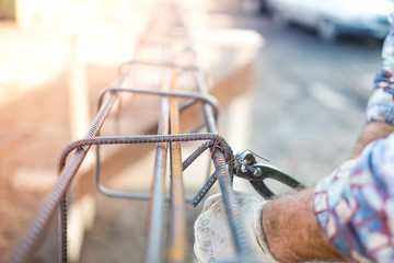 Construction worker securing steel bars with wire rod