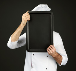 Portrait of chef with oven pan behind his face