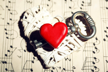 Retro key with hearts on music book background