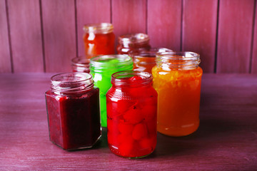 Homemade jars of fruits jam on color wooden background