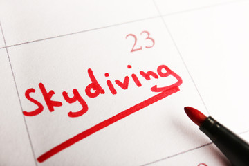 Written plan Skydiving on calendar page background
