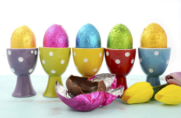 Chocolate Easter eggs in color foil in polka dot egg cups