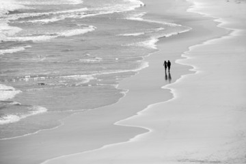 Couple walking along picturesque beach with waves
