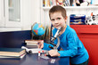 Boy with microscope at home