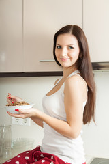 woman eating cereal in  kitchen