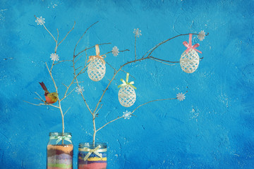 Home made Easter decoration on the background of a blue wall