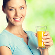 Smiling woman with orange juice, outdoors