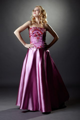 Studio photo of majestic blonde in pink dress