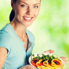 Smiling beautiful young woman with salad, outdoors
