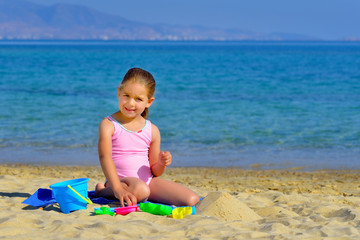 Toddler girl playing with her toys at beach