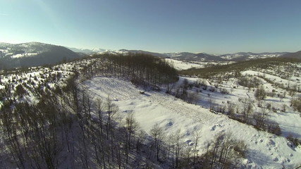 aerial flight up the hill in winter