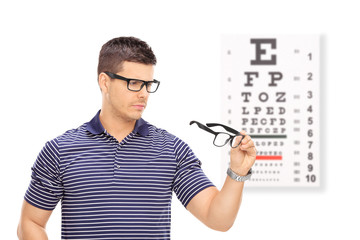 Man trying on glasses in front of an eye chart
