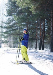 Sporty boy skiing in the forest, sunny winter day