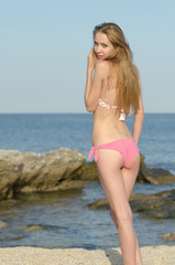Slim attractive blonde on beach, rocks and sea as background