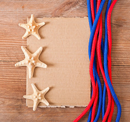 paper, rope and starfish on old wooden background