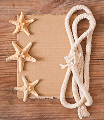 old paper, rope and starfish on old wooden background