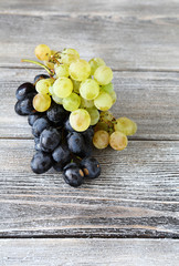 Two varieties of Sweet grapes on wooden background