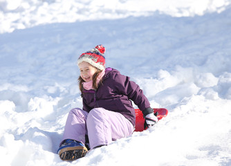 young girl plays with sledding on snow in the winter in the moun