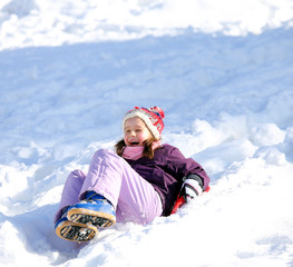 little girl plays with sledding on snow in the winter