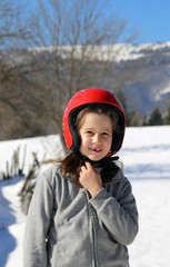 little girl with helmet in the winter