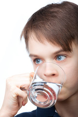 Cute boy drinking water on white background