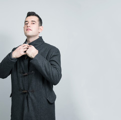 Portrait of a smart, fashion young man wearing a wool coat