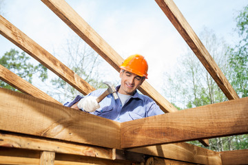 Worker Hammering Nail On Incomplete Timber Cabin At Site