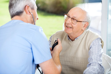Male Doctor Measuring Blood Pressure Of Senior Man