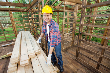 Smiling Carpenter Measuring Wooden Plank At Construction Site