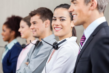 Customer Service Representative Standing With Colleagues And Man
