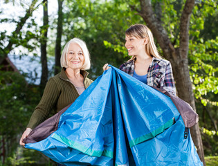 Mother And Daughter Making Tent In Park At Campsite