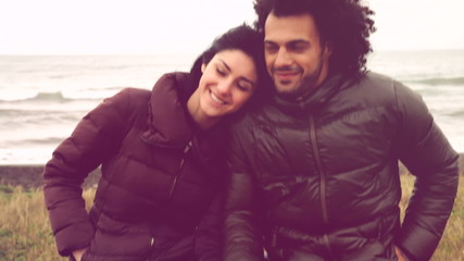Happy rcool omantic couple in front of ocean in winter
