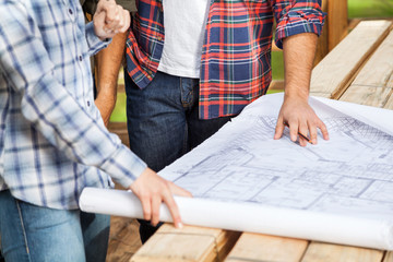 Carpenters Analyzing Blueprint At Site
