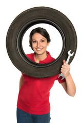 Junge Frau mit Reifen und Schraubenschlüssel