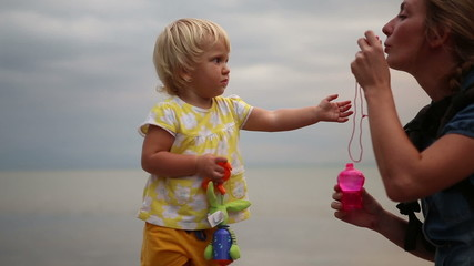 little blonde child comes up to mother blowing soap bubbles