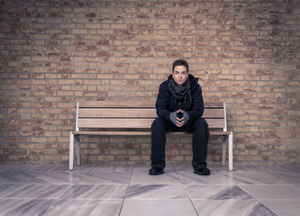 Young man(in black clothes) sitting on a bench