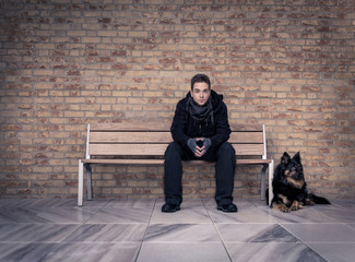 Young man sitting on a bench with your best four-legged friend