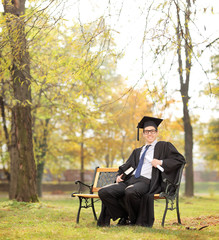 Graduate student holding diploma and book in park