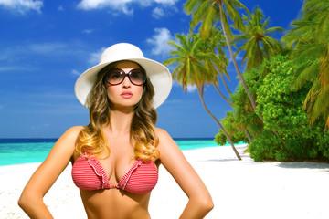 Bikini model with sunglasses on the tropical beach