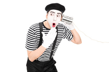 Mime artist listening through a tin can phone