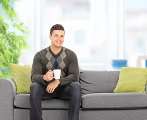 Young man drinking coffee seated on couch at home