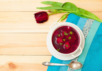 Red soup with dill in white bowl on wooden table with flower tul