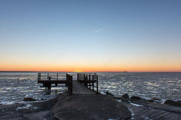 sunset over frozen sea with old metal bridge