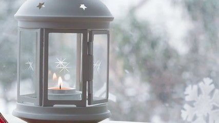 Lantern With Candle By The Window While Snowing