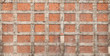 Texture of old house wall made of red bricks and concrete