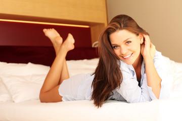 Junge, hübsche Frau liegt auf Bett