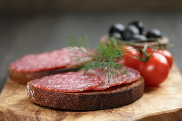 rye bread with salami on olive board