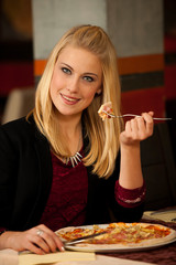 Beautiful young blond woman eating pizza in restaurant