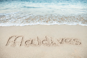 Maldives Written On Sand By Sea