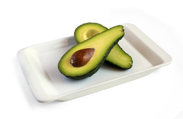 fresh avocado cut in half on square plate